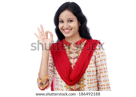 Happy young woman making Ok gesture against white background - stock photo