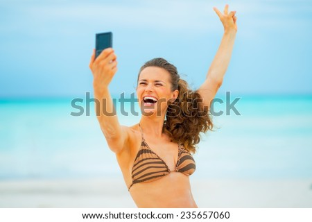 Happy young woman making selfie on beach - stock photo