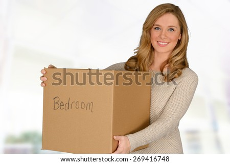 Happy young woman moving in carrying moving box - stock photo