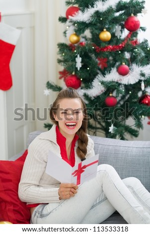 Happy young woman near Christmas tree reading postcard - stock photo