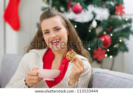 Happy young woman near Christmas tree with cup and cookie - stock photo