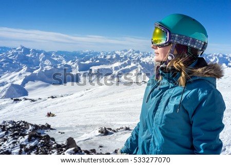 Happy young woman on background of the snowy high mountains and beautiful landscape