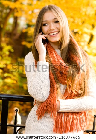 Happy young woman on cell phone in autumn park
