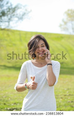 Happy young woman on cell phone in autumn park - stock photo