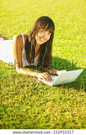 happy young woman on the grass with laptop