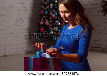 Happy young woman opening gift box near christmas tree. X-mas or New Year tree concept.