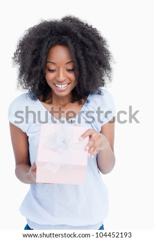 Happy young woman opening her birthday gift against a white background