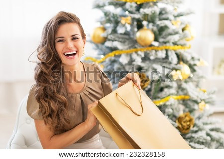 Happy young woman opening shopping bag near christmas tree - stock photo