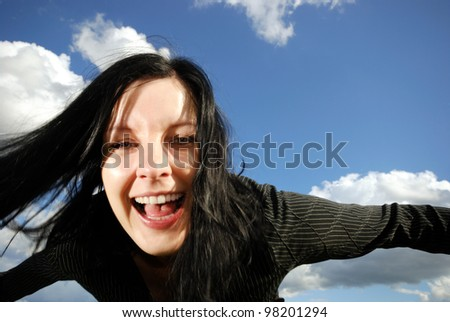 happy young woman outdoors against blue sky - stock photo