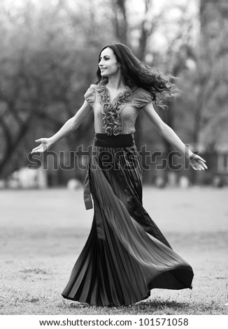 happy young woman outdoors in the field,dancing under the rain,black and white - stock photo