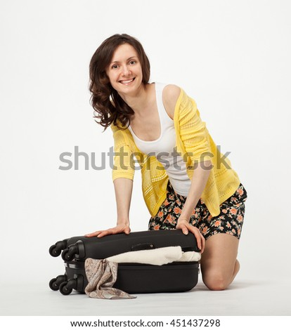 Happy young woman packing her overfilled suitcase - white background