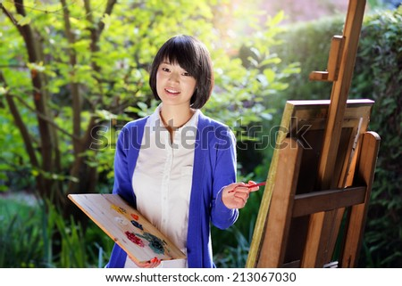 Happy young woman painting a canvas in the garden . Creativity and relax  - stock photo