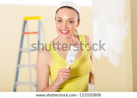 happy young woman painting new house - stock photo