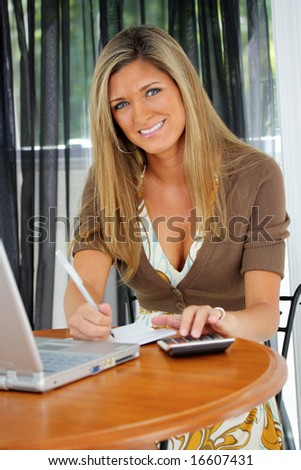 Happy young woman paying bills by computer - stock photo
