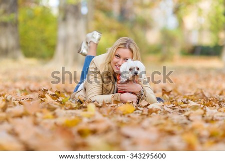 Happy young woman playing in the autumn leaves with her cute little dog - stock photo