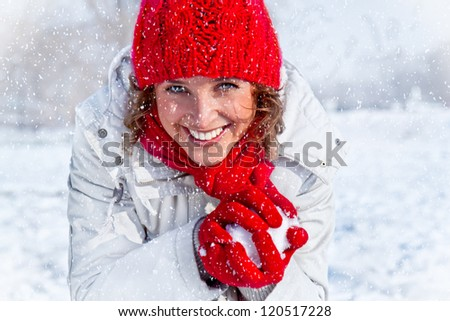 Happy young woman playing snowball fight on the snow day. Winter concept. - stock photo