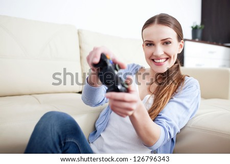 Happy young woman playing video games in living room