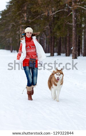 Happy young woman playing with siberian husky dog in winter forest - stock photo