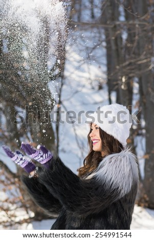 Happy young woman playing with snow outdoors on sunny winter day. Fashionable girl with fuzzy hat and coat throwing snow playing having fun. Vertical, no retouch, copy space. - stock photo