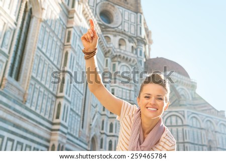 Happy young woman pointing in front of cattedrale di santa maria del fiore in florence, italy