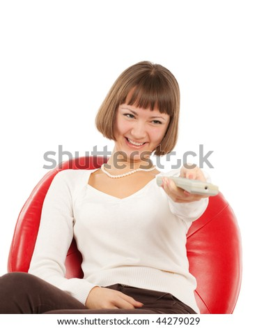 Happy young woman pointing remote control at TV - stock photo