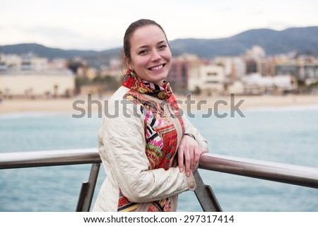 happy young woman posing at wharf and smiling - stock photo