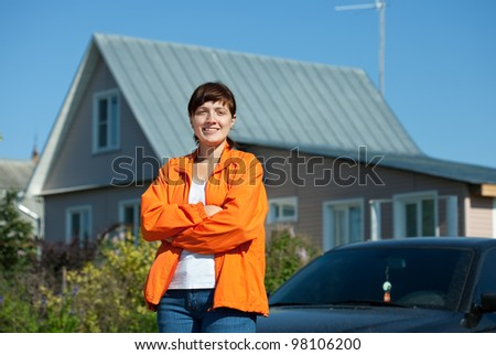 Happy young woman posing in front of her  residence - stock photo