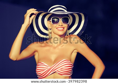 Happy young woman posing in hat and sunglasses - stock photo