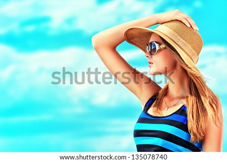 Happy young woman posing over blue sky. - stock photo