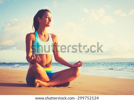 Happy young woman practicing yoga on the beach at sunset. Healthy active lifestyle concept. - stock photo