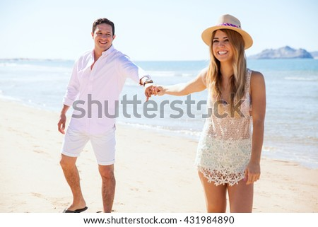Happy young woman pulling her boyfriend while holding hands and walking at the beach on their vacation - stock photo