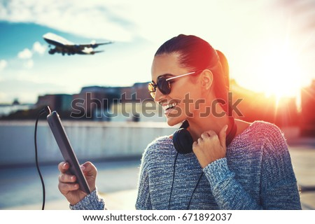 Happy young woman purchasing air ticket by tablet, outdoor in sunset