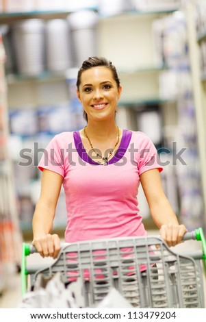 happy young woman pushing trolley in supermarket - stock photo