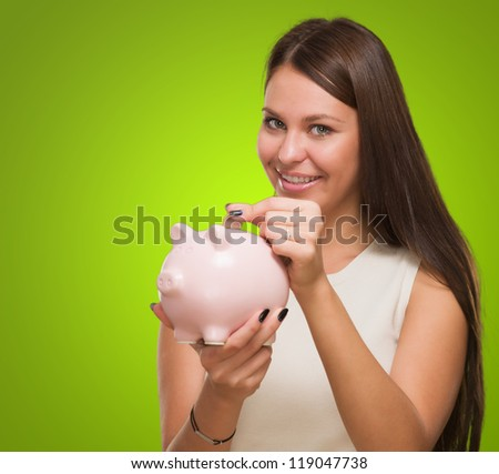 Happy Young Woman Putting Coin In Piggy bank against a green background