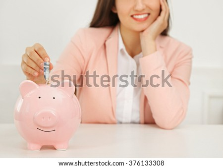 Happy young woman putting dollar banknotes into piggy bank. Money savings concept