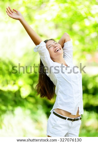 Happy young woman raising arms in park. Attractive mixed race Asian / Caucasian female is in casuals. She is closing eyes while smiling. - stock photo