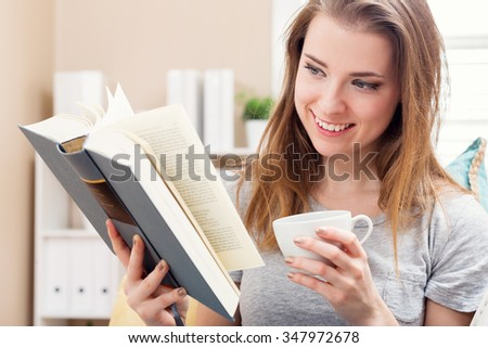 Happy young woman reading a book and drinking coffee on her couch at home