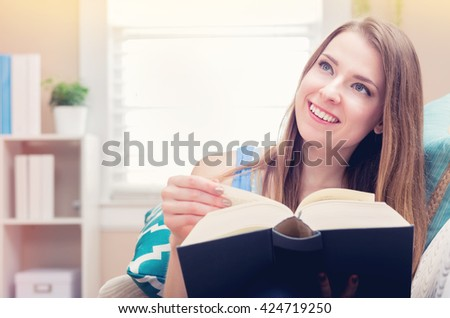 Happy young woman reading a book on her couch at home