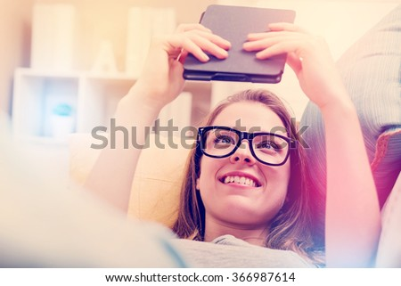 Happy young woman reading an e-book on her couch at home - stock photo