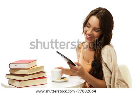 happy young woman reading ebook near books on white background - stock photo