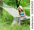 Happy young woman reading in hammock in green park summer outdoors background - stock photo