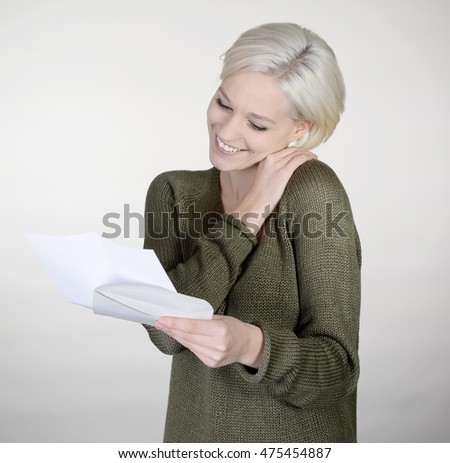 happy young woman reading letter, gray background