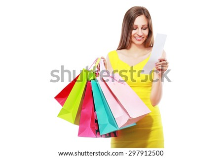 happy young woman reading receipt after good shopping and pointing at camera