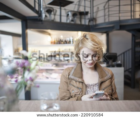 Happy young woman reading text message on cell phone in cafe - stock photo