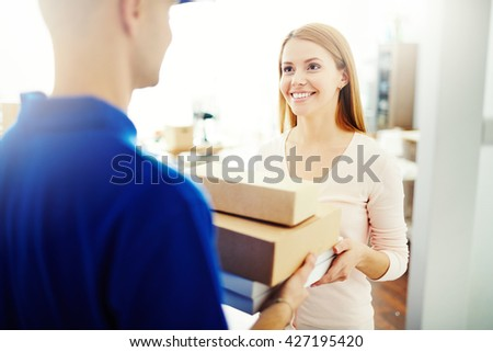 Happy young woman receiving a box from mailman - stock photo