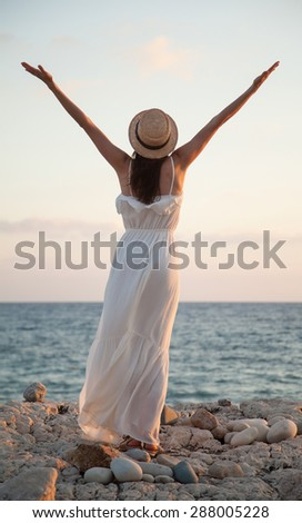 Happy young woman  rejoices at summer vacation and meets a daybreak - stock photo