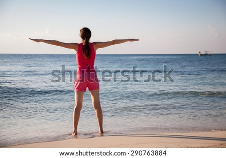 Happy young woman rejoices at summer vacation on the seacoast - stock photo