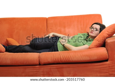 happy young woman relax on orange sofa  at home isolated on white background in studio