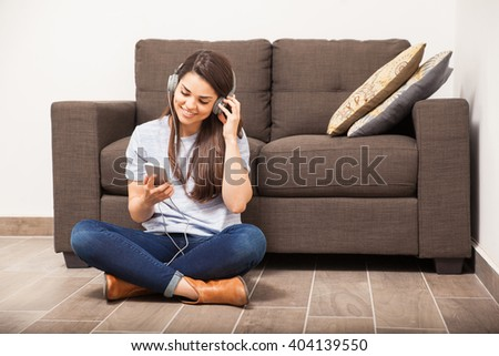 Happy young woman relaxing and listening to music using a streaming service on her smartphone - stock photo