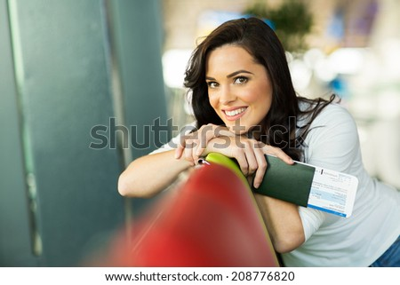 happy young woman relaxing at airport before boarding - stock photo